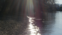 Lens flare over sparkling river shore Footage