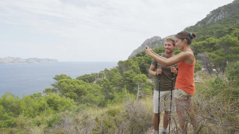 Hiking couple taking phone photo on nature hike using smartphone on Mallorca Live Action