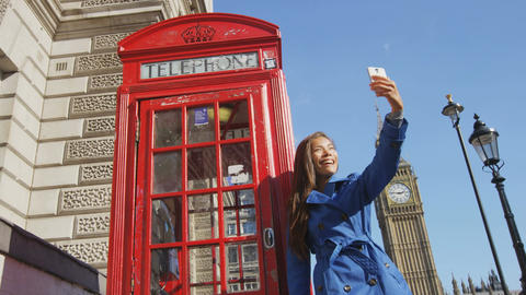 Young Urban Professional Woman on Taking Selfie by Phone booth by Big Ben London Footage