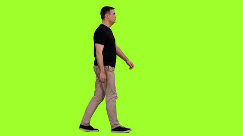 Adult man in black t-shirt walks on green screen background, Chroma key Footage