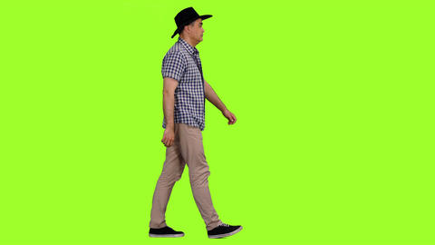 Adult man in plaid shirt and cowboy hat walks on green screen background Footage