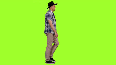 Adult man in plaid shirt and cowboy hat walks on green... Stock Video Footage