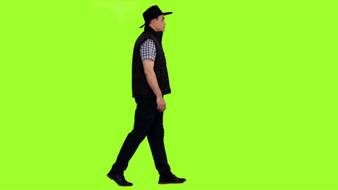 A man in a black vest and cowboy hat walks on green screen background Footage