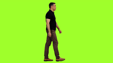 Side view of walking adult man on green screen background, Chroma key Footage