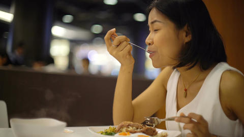 Beautiful Thai Woman eats pork with rice in restaurant Footage