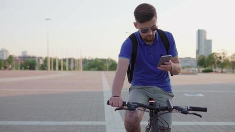 hipster man holding a smartphone and riding a bicycle Live Action