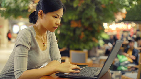 Young Thai Lady works on laptop in shopping mall toned video Filmmaterial