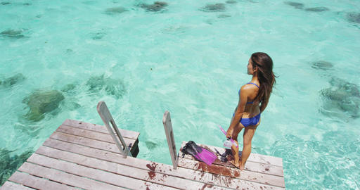 Swimsuit model relaxing on overwater villa deck on summer vacation destination Footage