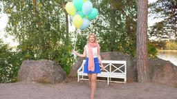 Young cheerful woman stand up and go with balloons in hand Footage