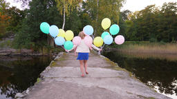 Young happy woman run to land along old pier, hold flying balloons, slowmo Footage