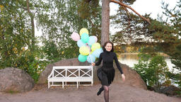 Young woman stand up from bench and run forward, balloons fly behind Footage