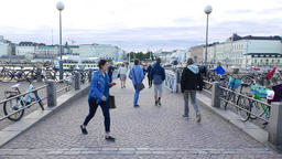 Pedestrian bridge at Helsinki port, people walk by, bicycles parked at handrails Live Action