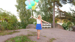 Happy young blonde woman hold many balloons and spin around Live Action