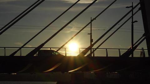 Modern tram ride on bridge, silhouetted view, sun shine through vehicle GIF