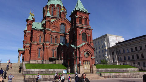 Asian tourists on square against Uspenski Cathedral, camera tilt up to building Footage