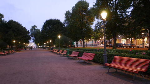 Empty wide walkway of Esplanadi park at evening twilight, wooden benches GIF