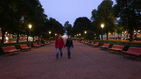 Couple stroll at evening park, man hold young woman by hand, walk towards camera GIF