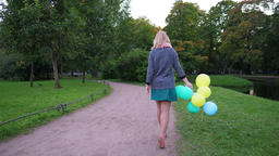Woman walk away with balloons in hand, alone at nice green park, evening time Live Action