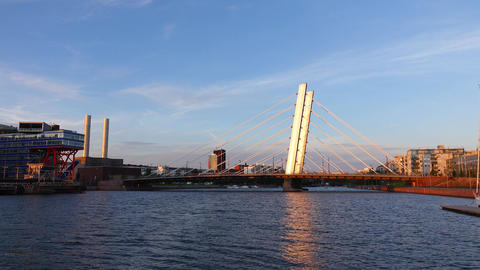 Calm city channel and cable stayed bridge span across, sunny evening Live Action