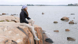 Thoughtful woman sit on large stone at Baltic sea shore, look at distance GIF