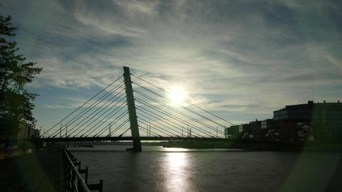 Silhouetted time lapse shot of modern cable-stayed bridge against evening sun Live Action