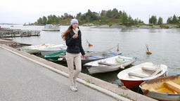 Woman eat ice cream and stroll along pier, small boats moored at bank Live Action