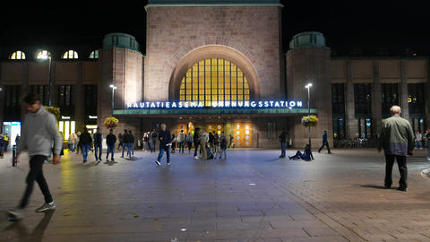 People walk around west entrance to Helsinki Central Railway station at evening Live Action