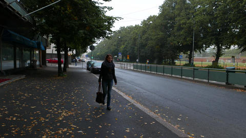Young woman walk alone at Helsinki street in dusk, autumn season GIF
