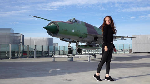 Slender woman pose against jet fighter aircraft set for display, slow motion Live Action
