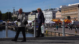 Mature couple go away, water side promenade at city square Live Action