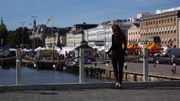 Young woman come and stay at Helsinki port embankment near market square Footage