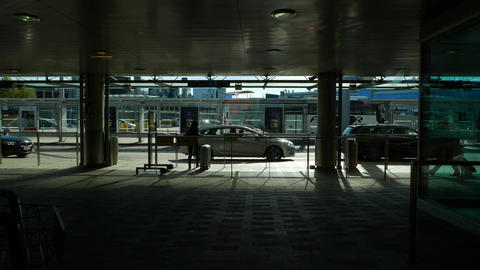 Empty shaded passage outdoors of airport exit, taxi cars queue, people pass by Footage