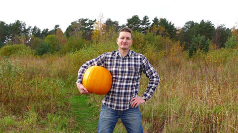 Farmer hold ripe orange pumpkin under arm, half-length portrait Footage