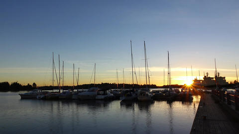 Sunrise over marina, dark yachts stay at jetty, sun move up and shine Footage