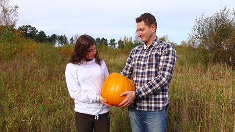 Handsome couple pose with ripe orange pumpkin, looking to camera GIF