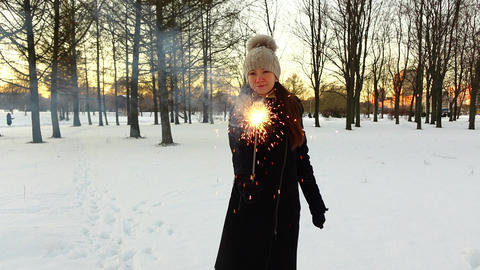 Woman with handheld firework stick at winter park, show sparkler to camera Live Action