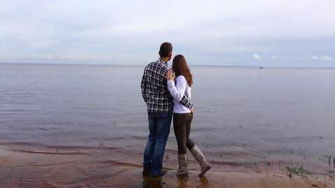 Lovely couple hug and look at lake horizon, shot from back GIF