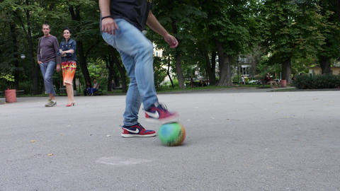 Man with casual clothes plays football tricks outside in city park Footage