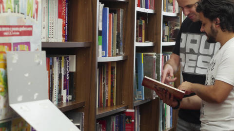 Friends discussing books in a library bookstore Footage