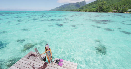 Swimming girl coming out of snorkel swim water in coral reefs of Tahiti ocean Live Action