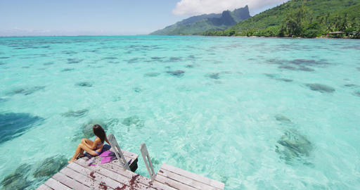 Travel woman relaxing on holiday sitting on overwater bungalow terrace Footage