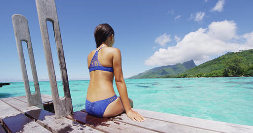 Bikini woman enjoying tropical vacation sitting after swim on overwater bungalow Footage