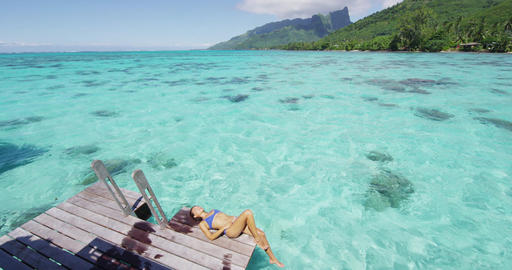 Luxury travel vacation destination bikini woman sunbathing at overwater bungalow Footage