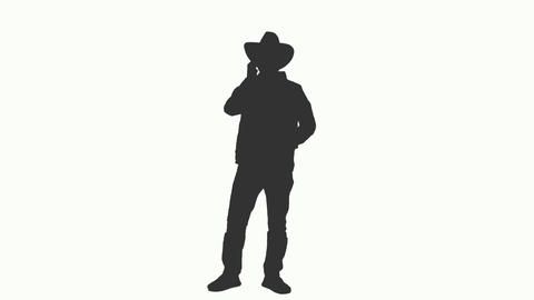 Silhouette of a man in cowboy hat talking on smartphone, alpha channel Footage