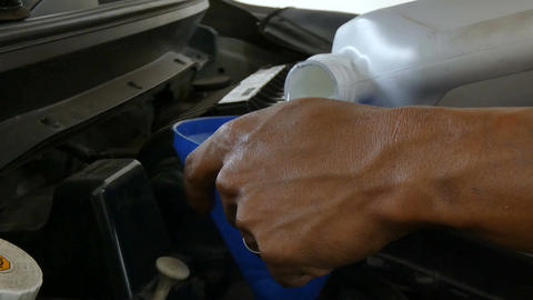 CLose up shot hands of mechanic filling engine lubricant oil in to car engine Footage