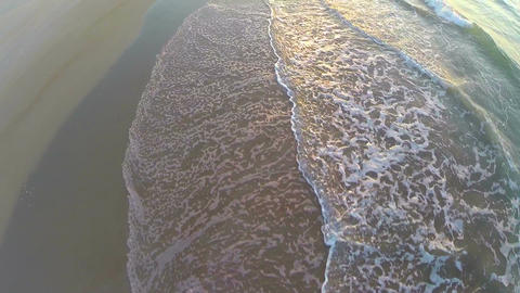 Aerial of sunrise tide rolling onto beach Live Action