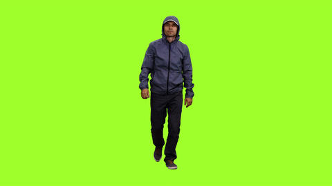 Front view of a hooded man walks on green screen background Footage