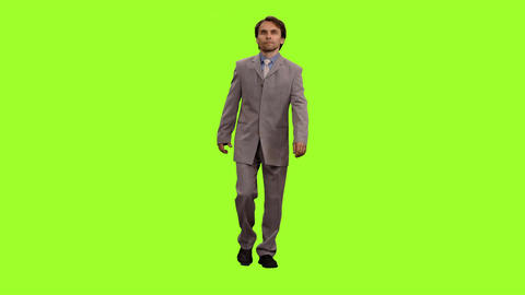 Front view of businessman in suit walks on green screen background Image