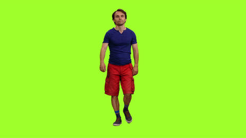 Male tourist in blue t-shirt and red shorts walks on green screen background Footage