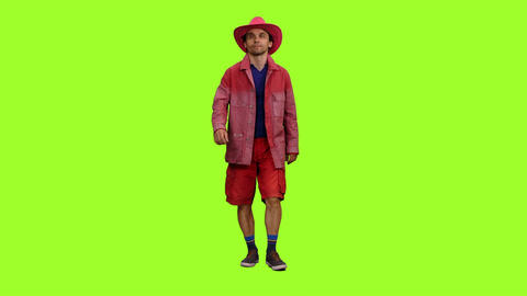 Man in red jacket, shorts and pink cowboy hat walks on green screen background ビデオ